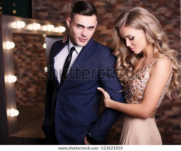 fashion studio foto van mooie sexy paar. prachtige vrouw met blond haar poseren met knappe man, het dragen van elegante kleding