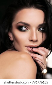 fashion studio photo of beautiful woman with dark hair and evening makeup