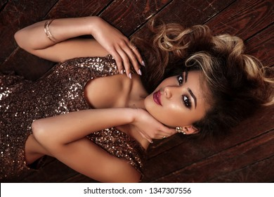 Fashion studio photo of beautiful young afro american woman with professional make-up wearing luxurious sequin dress