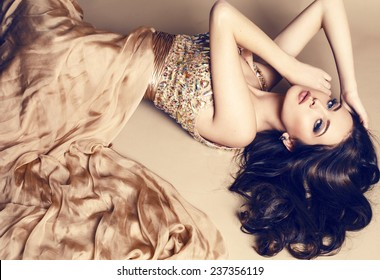 fashion studio photo of beautiful young girl with dark hair wearing luxurious beige dress,lying on the floor at studio