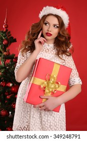 fashion studio photo of beautiful young girl with dark hair and charming smile wears Santa hat, posing with big present beside Christmas tree
