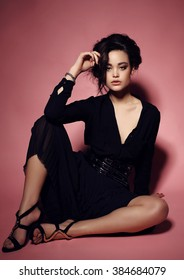 fashion studio photo of beautiful young woman with dark hair and evening makeup, wears elegant clothes