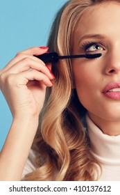 fashion studio photo of beautiful young woman with blond curly hair and bright makeup, holding mascara in hand