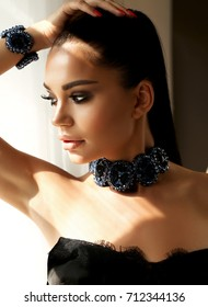 fashion studio photo of beautiful young girl with dark hair and evening smokey eyes makeup