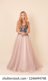 fashion studio photo of gorgeous beautiful woman with long blond hair in luxurious evening dress