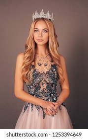 fashion studio photo of gorgeous beautiful woman, winner of beauty competition, with long blond hair in luxurious evening dress with crown on her head