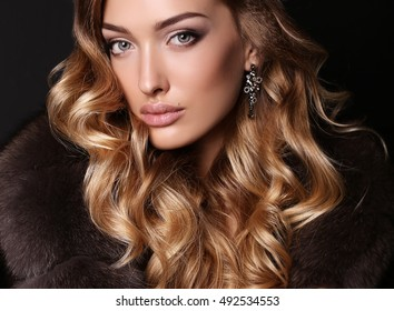 fashion studio photo of gorgeous sensual woman with blond hair in luxurious dress and fur coat