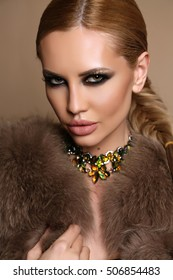 fashion studio photo of gorgeous sensual woman with blond hair and bright makeup, in elegant fur coat with bijou