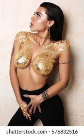 fashion studio photo of gorgeous sexy woman with dark hair posing nude, with body art gold painting