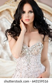 fashion studio photo of gorgeous young woman with dark curly hair and evening makeup wears luxurious beige dress