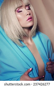 Fashion studio photo of sexy Asian beautiful girl in a wig of blond  hair wearing a blue cape wiht bright purple makeup enjoing and relaxing on the beige background