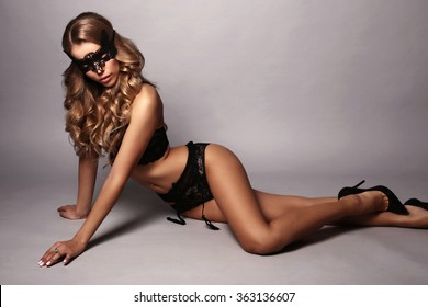 fashion studio photo of sexy gorgeous woman with long blond hair in black lingerie with lace mask on face