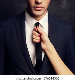fashion studio photo of sexy impassioned couple. handsome businesslike man in glasses,woman's hand holding his tie