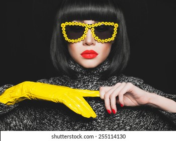 Fashion studio photo of stylish lady in gloves and sunglasses