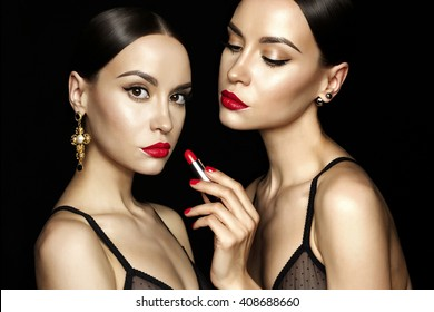 Fashion studio photo of two beautiful young ladys with red lipstick. Perfect face makeup. Beauty and jewelry