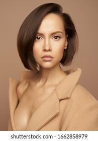 Modestudio-Foto einer jungen, schönen Dame mit beigem Mantel auf beigem Hintergrund. Beige insgesamt. Fashion Look Buch. Warmer Herbst. Warmer Frühling