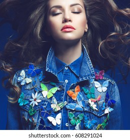 Fashion studio photo of young beauty woman  with a lot of brooches on her jeans jacket. Denim clothes. Jeans trend. Magnificent hair