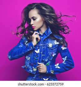 Fashion studio photo of young slim woman in jeans with a lot of brooches on her jeans jacket. Denim clothes. Jeans trend