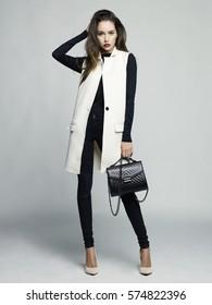 Fashion studio photo of young stylish woman. Elegant beige vest, black jeans and handbag, beige shoes. Catalogue clothes. Lookbook