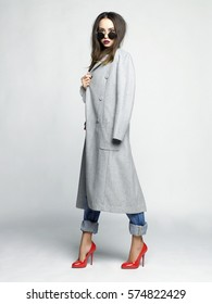 Fashion studio photo of young stylish woman. Grey oversize coat, white shirt, blue jeans, red shoes and handbag. Catalogue clothes. Lookbook
