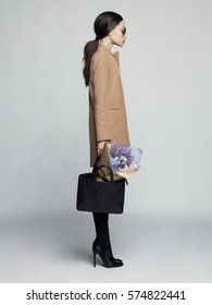 Fashion studio photo of young stylish woman. Beige coat, black leather boots and bag, bouquet of lavender. Catalogue clothes. Lookbook