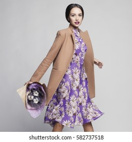 Fashion studio photo of young stylish woman. Beige coat, lilac dress, bouquet of lavender. Catalogue clothes. Lookbook