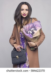 Fashion studio photo of young stylish woman. Beige coat, textile bag, lilac dress, bouquet of lavender. Catalogue clothes and accessories. Lookbook