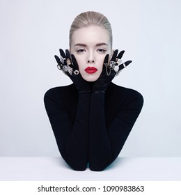 Fashion studio portrait of beautiful blonde lady with lot of precious rings. Conceptual photo. Jewelry
