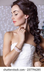 fashion studio portrait of beautiful bride with long dark hair in elegant wedding dress with accessories posing in decorated studio with Christmas tree on background