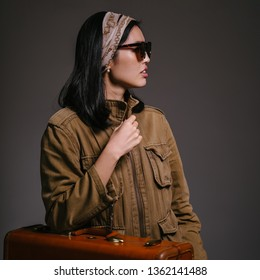 Fashion studio portrait of a beautiful, elegant and sophisticated Korean Asian woman socialite in a brown jacket and sunglasses standing next to her brown leather suitcase. She looks glamorous.