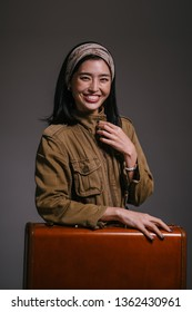 Fashion studio portrait of a beautiful, elegant and sophisticated Korean Asian woman socialite in a brown jacket and sunglasses smiling next to her brown leather suitcase. She looks glamorous.