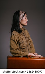 Fashion studio portrait of a beautiful, elegant and sophisticated Korean Asian woman socialite in a brown jacket standing next to her brown leather suitcase. She looks glamorous.
