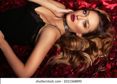 fashion studio portrait of beautiful girl with blond curly hair and evening makeup, lying among rose petals