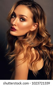 fashion studio portrait of beautiful girl with blond curly hair and evening makeup