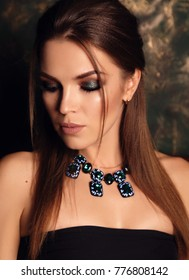 fashion studio portrait of beautiful girl with dark hair and evening makeup