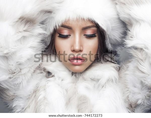 Fashion studio portrait of beautiful lady in white fur coat and fur hat. Winter beauty in luxury. Fashion fur. Beautiful woman in luxury fur coat. Fashion model posing in eco-fur coat and eco-fur hat