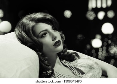 Fashion studio portrait of beautiful sensual woman with curly hair, black and white photography in retro style