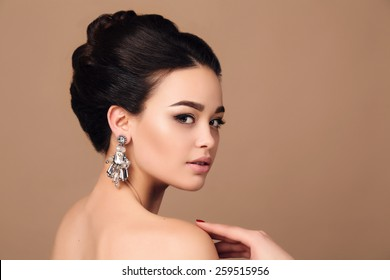 fashion studio portrait of beautiful sexy woman with dark hair and evening makeup,with bijou
