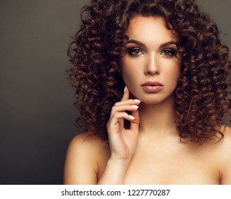 Fashion studio portrait of beautiful smiling woman with afro curls hairstyle. Fashion and beauty