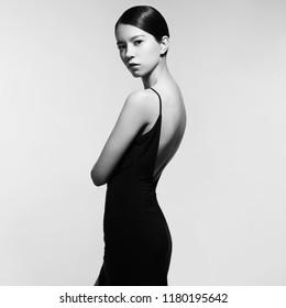 Fashion studio portrait of beautiful woman in black evening dress. Asian beauty.