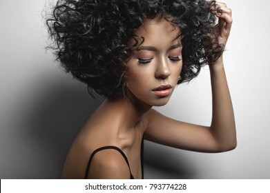 Fashion studio portrait of beautiful woman in black dress with afro curls hairstyle. Fashion and beauty