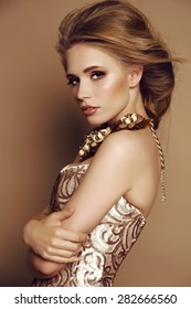 fashion studio portrait of beautiful young girl with blond hair and bright makeup with accessories