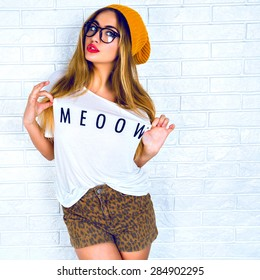 Fashion studio portrait of beautiful young blond hair women making face a cap, white t-shirt and shorts with glasses and red lips against a white wall.