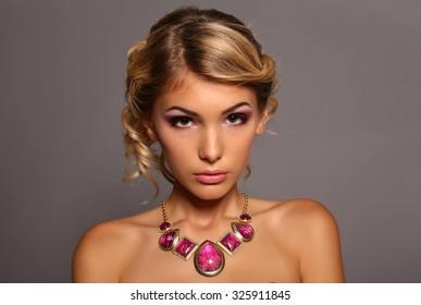 fashion studio portrait of beautiful young woman with elegant hairstyle and bijou