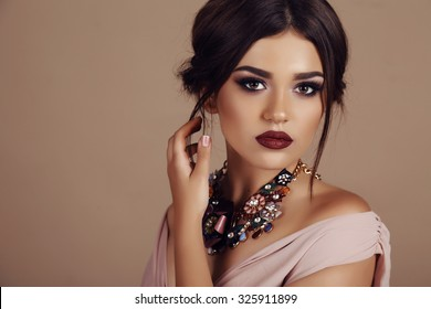 fashion studio portrait of beautiful young woman with elegant hairstyle and luxurious necklace