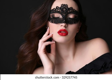 fashion studio portrait of beautiful young woman with luxurious dark hair and evening makeup,with black lace mask on face