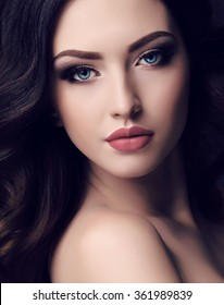 fashion studio portrait of beautiful young woman with long dark hair and blue eyes with bright makeup