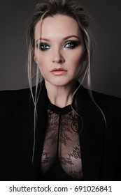 fashion studio portrait of beautiful young girl with blond hair and bright makeup