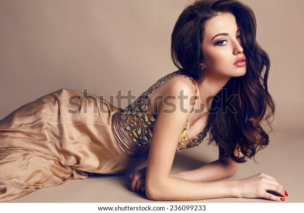fashion studio portrait of beautiful young girl with dark hair wearing luxurious beige dress