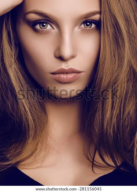 modestudio portret van mooie jonge vrouw met donker haar en groene ogen